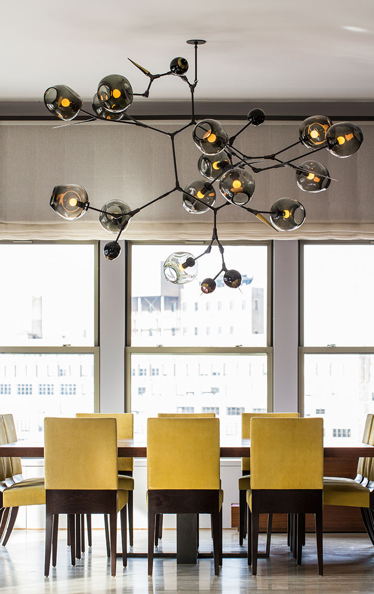 Yellow dining chairs and a huge Branching Bubbles chandelier by Lindsay Adelman